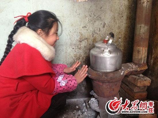 一位小姑娘正在烧煤炉子旁取暖