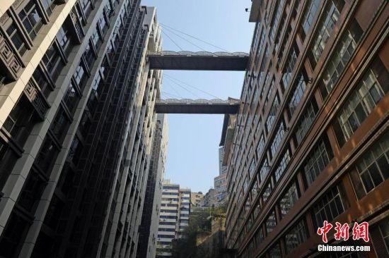 人行天橋距離地面68米。   近日,重慶渝中區解放碑臨江門附近一家新建樓盤上,懸空架起了兩座空中天橋。據了解,兩座空中天橋是平行的,一側連接渝中區嘉濱路118號高盛創富中心B棟22樓,一側連接奎星樓廣場。目前僅其中一條可供通行,另一條被鐵鏈鎖住。該空中連廊橋身兩側共有8根鋼繩承重,鋼繩一頭固定于橋身,另一頭固定在B棟大樓墻面上。形成一個斜拉人形天橋,據工程方介紹,為了安裝這兩座鋼結構人形天橋,采用了起重150噸重的大吊車,才完成了安裝,人行天橋距離地面68米。從嘉濱路到臨江門,以前要走20多分鐘?,F在有了