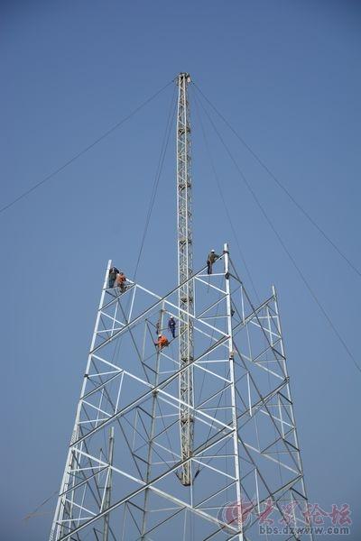 电力工人正在野外安装电力输送铁塔
